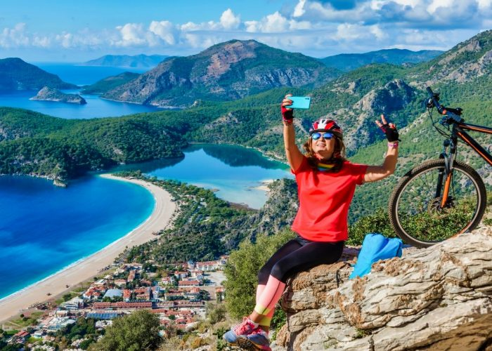 Women takes selfie in a beautiful landscape with a cycle